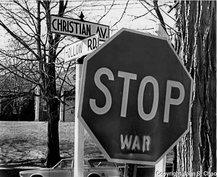 With a message relevant through history, a B&W photo taken in late 1968 during the Vietnam War, of a traffic stop sign with graffiti protest, by intersection signs of Christian Avenue and Hollow Road. Continuing past the sign is on Hollow Road, but turning, is onto Christian Avenue. Stony Brook, New York. A timeless cameo of America's penchant for militaristic politics and history's lost lessons.  ..