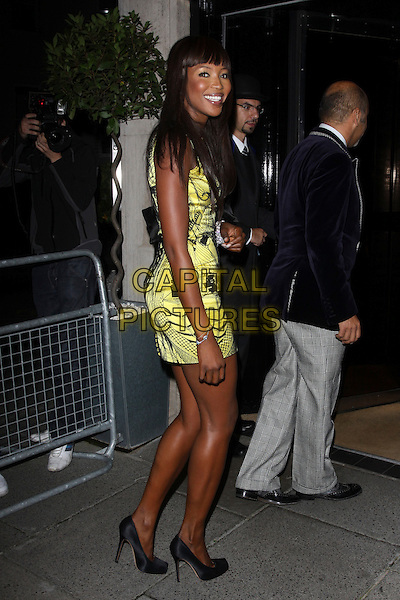 NAOMI CAMPBELL.The Vogue Dinner Party at La Caprice Restaurant, London, England..September 21st, 2009.full length black yellow mini dress sleeveless print pattern looking over shoulder .CAP/AH.©Adam Houghton/Capital Pictures.