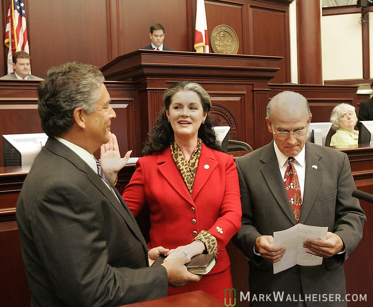 "Represenative Marty Bowen, center, from Haines City, looks at her husband, Brian Barnard, of Tallahassee, holding the Bible as she takes the oath of office of Speaker Pro-Tempore being administered by William ""Bo"" Pittman lll, right, the Chief Clerk of the House during the legislative special session called to deal with the issue of  tax relief at the Florida Capitol in Tallahassee, Florida June 12, 2007.  Both the House and Senate met for less than 30 minutes before adjourning.  (Mark Wallheiser/TallahasseeStock.com)"