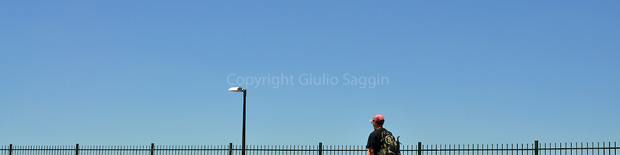 A man walks past a fence at the Fortitude Valley end of the Story Bridge in Brisbane.