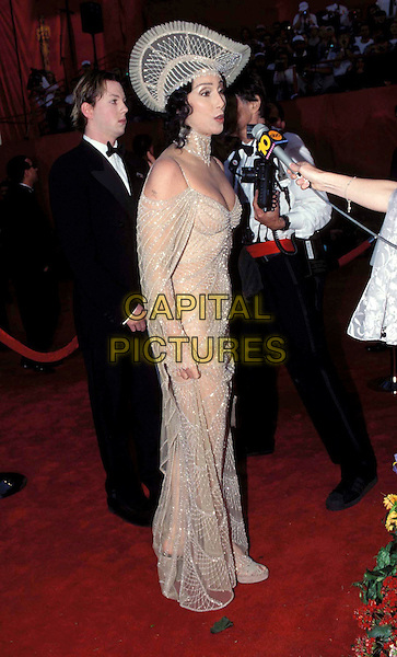 CHER.Academy Awards 1998.Ref: 7237.fashion disaster, oscars, hat, red carpet, crochet dress, full length, full-length.www.capitalpictures.com.sales@capitalpictures.com.© Capital Pictures