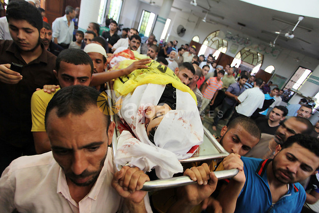 Palestinians carry the body of Ahmed Al-Masri, 14, who witnesses said was killed in an Israeli airstrike, during his funeral in Deir Al-Balah town in Central Gaza Strip, August 10, 2014. Palestinian negotiators will remain in Cairo for an urgent meeting with the Arab League on Monday to discuss the Gaza crisis, Egypt's state MENA news agency said. The Palestinian delegation had said it was likely to abandon Egyptian-mediated talks on Sunday unless Israel agreed to return to the table without pre-conditions. Photo by Ashraf Amra