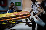 """Paramedics push a blood-soaked gurney from a shooting victim at Roosevelt Hospital in Guatemala City, on Saturday, May 5, 2012. The police named the victim, who was a truck driver, """"dos equis"""", or dbl XX (meaning, without name) because he carried no identification. The police sprayed his truck and shot the driver when he did not stop at a checkpoint."""