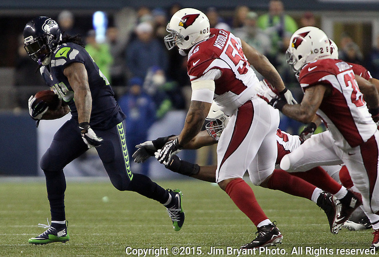 Seattle Seahawks running back Marshawn Lynch rushes past  Arizona Cardinals Calais Campbell (93), Deone Johnson (20),  LaMarr Woodley (56) and Tyrann Mathieu (32) at CenturyLink Field in Seattle, Washington on November 15, 2015. The Cardinals beat the Seahawks 39-32.   ©2015. Jim Bryant photo. All Rights Reserved.