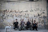 "Rebel fighters belonging to the Kateba Omar Ben Abdul Aziz pose proudly in front of a wall tagged with the name of their batallion and the legend ""we will die or we die"" at the Aamria battlefield embedded inside a civilian neighborhood at the southwest of Aleppo City. ."