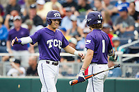 TCU Horned Frogs third baseman Derek Odell (5) is greeted by teammate Cody Jones (1) after scoring against the LSU Tigers in Game 10 of the NCAA College World Series on June 18, 2015 at TD Ameritrade Park in Omaha, Nebraska. TCU defeated the Tigers 8-4, eliminating LSU from the tournament. (Andrew Woolley/Four Seam Images)