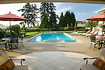 An peaceful, late summer afternoon view of a beautifully manicured, poolside landscape featuring lush green grass lawn, containers of mixed annuals, a long beautiful blue swimming pool with built in tiled spa glowing blue in the sunshine, and matching chaise lounge chairs and dining tables with orange red umbrellas in this Northwest summer scene in a suburban community east of Seattle.