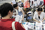 A man reads a manga book during the ''Comic Market 88 Summer 2015'' exhibition at Tokyo Big Sight on August 14, 2015, Tokyo, Japan. Thousands of manga and anime fans attended the first day of the Comic Market 88 (Comiket) at Tokyo Big Sight. The Comic Market was established in 1975 to allow fans and artists to interact and focuses on manga, anime, gaming and cosplay. The exhibition is held from August 14th to 16th and Comiket organisers expect more than 500,000 visitors to attend. (Photo by Rodrigo Reyes Marin/AFLO)