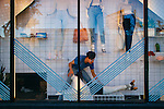 Visual Manager Will Gomez (in blue) decorates the window display at the American Apparel store located on Sunset Boulevard in the Echo Park neighborhood of Los Angeles, California February 6, 2015.