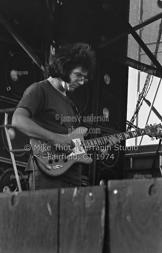 Jerry Garcia looking down at his work while playing Guitar with The Grateful Dead at Dillon Stadium in Hartford CT on 31 July 1974. Close in quarter view shot. Wall of Sound behind. Photo by Michael Thut, Fairfield CT.