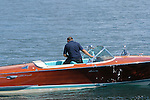 A man drives a wooden speed boat that has teal seats and a beautiful shiny wooden surface near Tremezzo, a town on Lake Como, Italy.