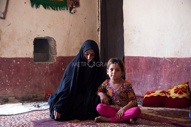 ABU AL-NRSI, IRAQ: Hania and her mother in their house. Hania's father was killed in Fallujah during the sectarian violence...Dozens of families displaced by years of violence have been forced to return to the district of Chebaish...Photo by Ali Arkady/Metrography