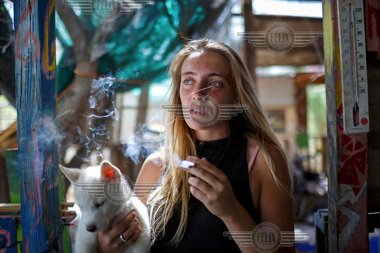 20 year old Hannah smoking weed. She was a carpenter when she left her hometown, New York in January 2017. She arrived in Slab City in February 2017 and after meeting her boyfriend Zack, her one week stay became longer. Hannah is the only child and her family members are scattered across the United States. Her mother re-married a few years ago and her father is marrying another man in September and Hannah will be walking him down the aisle. <br /> <br /> 'I don't like the snow and cold. I don't like the hot desert either. I have read books on Buddhism and they give me serenity. When I found my dog, I was feeling lost and confused so I named him Buddha.'<br /> <br /> Slab City, known as The Slabs, is named for its areas of concrete where for many years, since the military based closed, people have parked their RVs as they travel south for the winter. There is also a permanent community of 'Slabbers', around 200 people, who have established themselves living free in the Sonoran Desert where temperatures can reach 48 Celsius in the summer and, while there is no rent, there is also no water, electricity or services. Slabbers are an eclectic bunch often escaping poverty but also holding in common the desire to escape the rules and order of society in what they like to call 'the last free place on earth'.