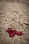 Red sandals lying on a beach