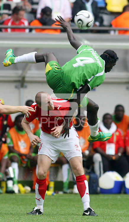 Togo's Emmanuel Adebayor (4) goes up for a header over Switzerland's Philippe Senderos (bottom). Switzerland defeated Togo 2-0 in their FIFA World Cup Group G match in Dortmund, Germany, June 19, 2006.
