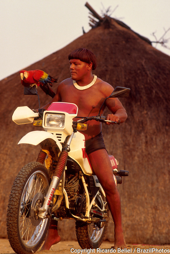 Acculturated brazilian indian, Xingu, Amazon rainforest, Brazil. Yaulapiti Indigenous People. Native rides a motor cycle ( motorcycle ) and holds a red macaw in front of a traditional native house. Multi-culturalism, mix of traditional culture and influence of the white culture.
