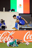 Jonathan Lopez (24) of Guatemala jumps over the tackle of Carlos Salcido (3) of Mexico. Mexico defeated Guatemala 2-1 during a quarterfinal match of the 2011 CONCACAF Gold Cup at the New Meadowlands Stadium in East Rutherford, NJ, on June 18, 2011.