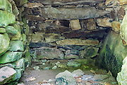 Abandoned cellar hole along an old dirt road, near Black Brook, in Warren, New Hampshire. Based on an 1860 historical map of Grafton County this was the homestead of S.T. Hayt. This is inside the split stone arch that supported the chimney structure. Consisting of two walls of stones topped with horizontal stones this type of chimney arch was used after the turn of the nineteenth century. And it has been documented that farmers used this area for winter food storage.