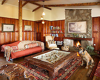 A sitting room in a luxury cottage guest house, which has a rustic feel. The talents of regional artists provide many of the finishing touches. A low wooden coffee table with a glass top containes a display of animal bones. A lit fire in the stone fireplace gives a cosy feel.
