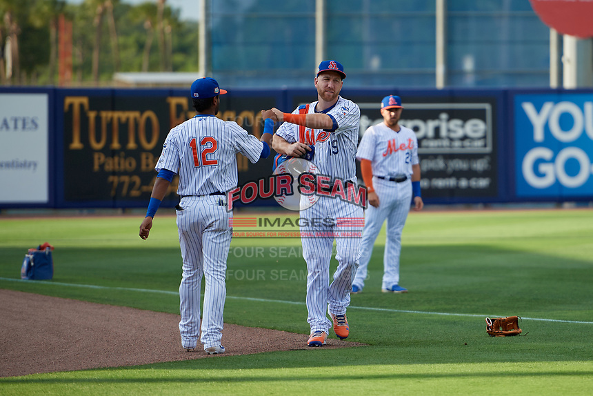 St. Lucie Mets Todd Frazier (19), on rehab assignment, fist bumps Luis Carpio (12) during warmups before a Florida State League game against the Florida Fire Frogs on April 12, 2019 at First Data Field in St. Lucie, Florida.  Florida defeated St. Lucie 10-7.  (Mike Janes/Four Seam Images)