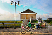 A man sleeps in a chair, as a girl rides past a  bicycle in Atlantic City, USA.