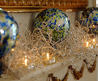 Blue and green baubles, frosted decorations and tealights decorate a mantelpiece in the living room