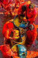 Filling containers with colored liquids from vats that will be thrown and sprayed with squirters onto crowds at Lathmar Holi (Festival of Colors), Nandgaon, Uttar Pradesh, India.
