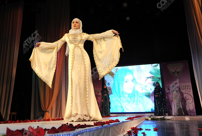 A model came down the catwalk of a fashion show and competition to choose the best Chechen designers in Grozny, the Chechen capital, on the day of president Ramzan Kadyrov's wife's birthday, whose portrait was on the screen in the background. September 7, 2011