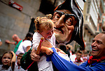 A man dressed as a giant holds a young girl during the giants and big heads parade of the San Fermin festival, on July 10, 2012, in the Northern Spanish city of Pamplona. The festival is a symbol of Spanish culture that attracts thousands of tourists to watch the bull runs despite heavy condemnation from animal rights groups . (C) Pedro ARMESTRE . (c) Pedro ARMESTRE