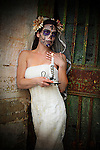 Photograph of a young woman posing by the door entrance of a mausoleum. She is in a white bridal dress with a veil and has two large flowers in her hair. She also has sugar skull makeup on and is holding a lit courting candle.