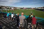 Home supporters watching the early action at the Mersey Travel Arena, home to Marine Football Club (in white), as they played host to Ilkeston FC in a Northern Premier League premier division match. The match was won by the home side by 3 goals to 1 and was watched by a crowd of 398. Marine are baed in Crosby, Merseyside and have played at Rossett Park (now the Mersey Travel Arena)  since 1903, the club having been formed in 1894.