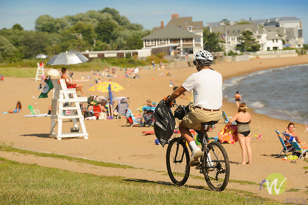Garvin Beach Park, Madison, CT. Senior man riding bike.