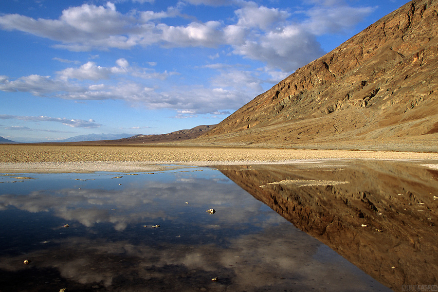 A rocky slope is reflected in the shallow waters of Badwater Basin, the lowest spot in North America at 282 feet below sea level, in Death Valley National Park, California.