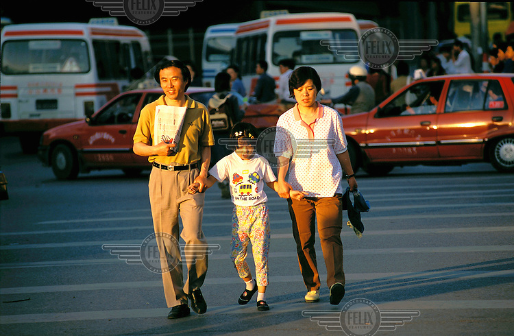 Mark Henley/Panos Pictures..China, Beijing..Parents crossing teh road with their daughter.