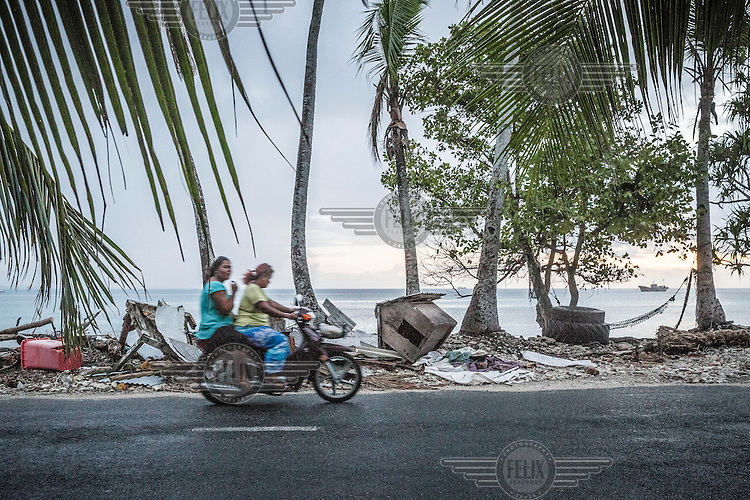 Women riding a scooter in Funafuti, Tuvalu's capital.  Tuvalu has a population just over 10,000 people, most of whom live in the country's capital Funafuti. Increasing urbanisation, along with climate change, pose big threats to this tiny Pacific country. Migration from the outer islands to the main island of Fongafale is placing increasing pressure on water supplies and land availability, while employment opportunities in the small formal sector are limited. Moreover, stronger 'King Tides', Saltwater intrusion into the groundwater and extreme weather events are making this island nation one of the most vulnerable countries in the world.