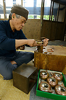 "Goro Hosono, ""tsuiki"" copperware artisan working on the handle for a copper kettle. Gyokusendo, Tsubame, Niigata Pref, Japan, August 24, 2017. Traditional copper metalworking company Gyokusendo was founded in 1816 and is a registered as a traditional craft of Japan. At Gyokusendo, in a highly-skilled craft process, complex items such as teapots are beaten from a single sheet of copper using hammers and hundreds of other specialist tools."