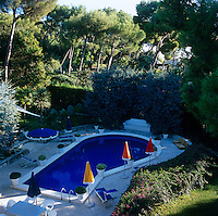 Aerial view of the swimming pool and surrounding terrace with sun-loungers and brightly coloured umbrellas