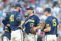 Michigan Wolverines pitcher Jeff Criswell (17) talks to  pitching coach Chris Fetter (41) against the Vanderbilt Commodores during Game 3 of the NCAA College World Series Finals on June 26, 2019 at TD Ameritrade Park in Omaha, Nebraska. Vanderbilt defeated Michigan 8-2 to win the National Championship. (Andrew Woolley/Four Seam Images)