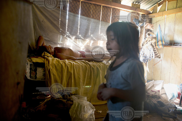 A Waorani (Huaroni) man lies on his bed in a house with a young girl standing nearby.