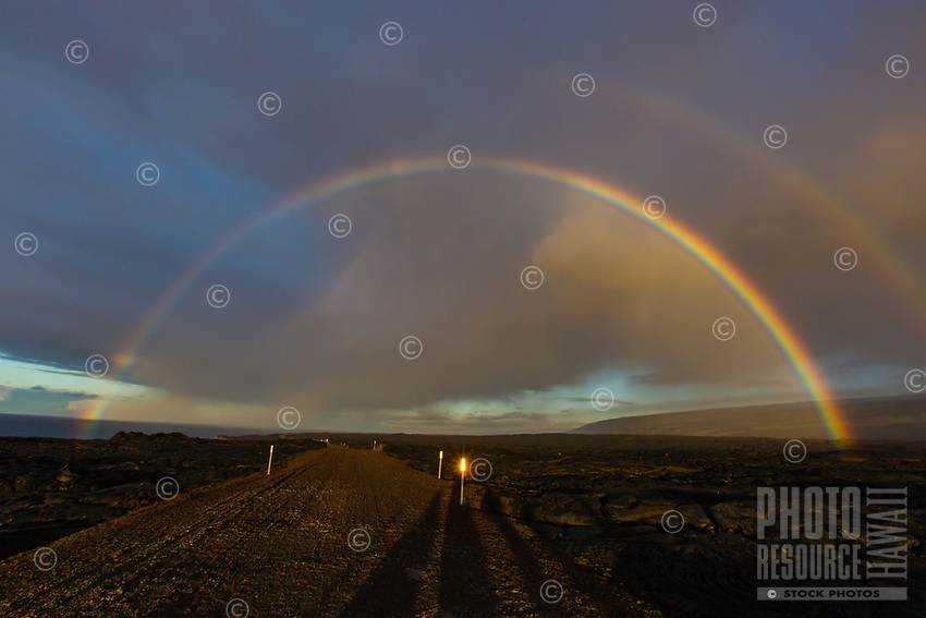 Double rainbow over a long dirt road with white markers on the Big Island of Hawai'i.