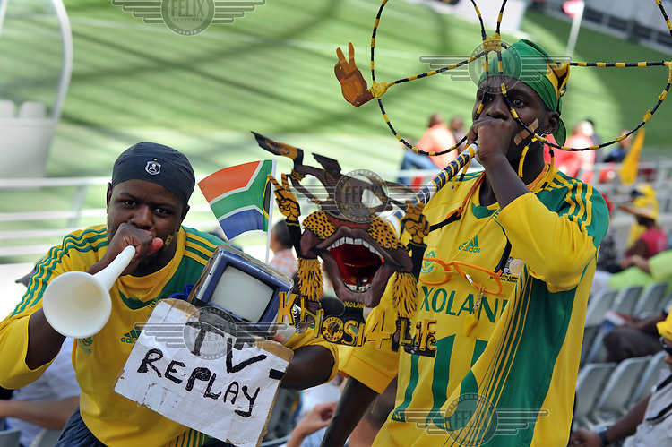 Fans blow vuvuzelas (plastic horns), a staple of South African football, at the opening match at Cape Town's new 2010 FIFA World Cup football stadium. One fan also carries a small television, joking that he will be able to replay any controversial incidents in the match. 20,000 fans flocked to the stadium for its first public event since completion in December 2009. The stadium seats 68,000 and the first test event was used to check that all systems, transport, security, staffing and logistics worked satisfactorily.