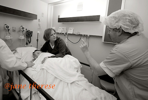 As Drew sleeps of the anesthesia, Dr. James Murphy, the pediatric surgeon who extracted Drew's teeth, discusses the outcome of Drew's surgery with Drew's mother Jill. Drew was admitted to Doylestown Hospital for Out Patient Same Day Surgery for an extraction of teeth, due to an overcrowded mouth. Braces would have been an option for Drew, had he not been autistic. photo by jane therese