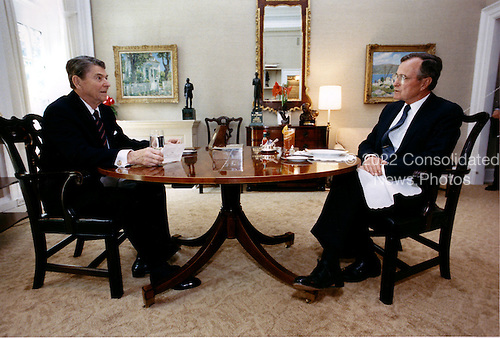Washington, D.C. - April 27, 1988 -- United States President Ronald Reagan and Vice President George H.W. Bush meet for their weekly lunch in the Oval Office Study at the White House in Washington, DC on April 27, 1988..Credit: White House via CNP