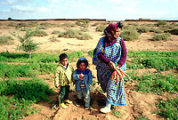 Women picking carrots with children