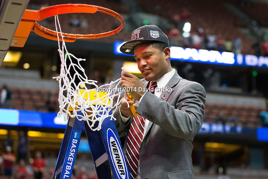 Wisconsin Badgers assistant coach Lamont Paris cuts down a piece of the net after the Western Regional Final NCAA college basketball tournament game against the Arizona Wildcats Saturday, March 29, 2014 in Anaheim, California. The Badgers won 64-63 (OT). (Photo by David Stluka)