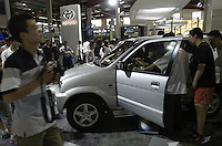 Visitors look at a Toyota Dario at the Auto China 2004 exhibition in Beijing, China..