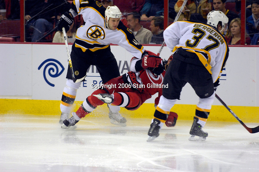 Carolina Hurricane captain Rod Brind'Amour is leveled by the Boston Bruins' Andrew Albertson, left, as teammate Patrice Bergeron looks for the puck during an NHL hockey game Saturday, Dec. 2, 2006 in Raleigh, N.C. Carolina won 5-2.<br />