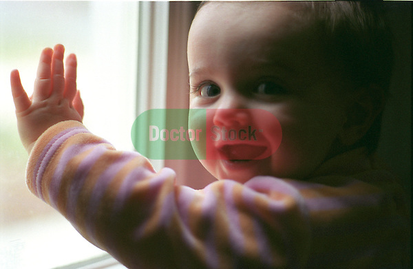 7 month old girl with hand up to a window face turned toward camera