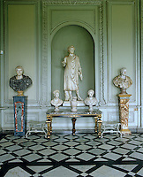 The entrance hall at Petworth House has an impressive marble floor in a geometric pattern and is graced with a collection of busts and statues