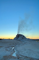 Small geyser erupts at sunset-Firehole Lk. area-Yellowstone National Park, Wyoming